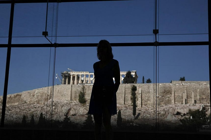 A woman looks at exhibits on display in the Parthenon hall at the Acropolis museum, as the temple of the Parthenon is seen in the background, in Athens, Greece on Oct 10, 2014. -- PHOTO: REUTERS