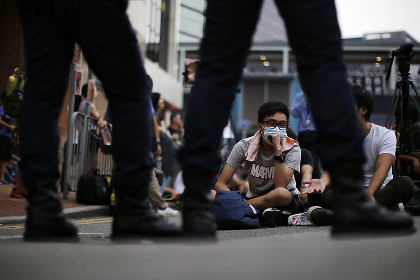Pro-democracy protesters sit facing policemen as the block an area near the government headquarters building in Hong Kong on Oct 14, 2014. -- PHOTO: REUTERS
