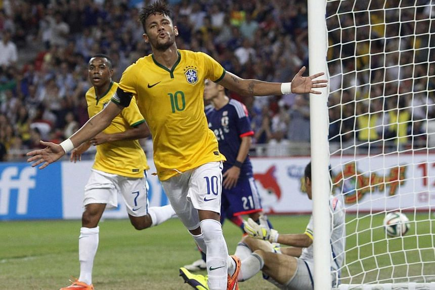 Brazil's Neymar celebrates after his fourth goal against Japan during their friendly soccer match at the national stadium in Singapore on Oct 14, 2014. -- PHOTO: REUTERS