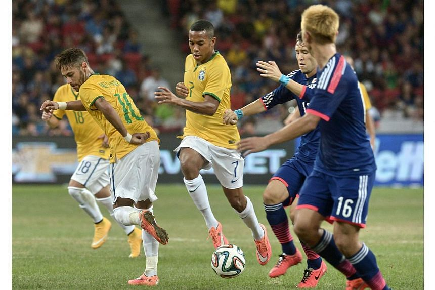Brazil's forward Neymar (left) passes the ball to teammate Robinho (2nd left) in a friendly football match against Japan at the National stadium in Singapore on Oct 14, 2014. -- PHOTO: AFP