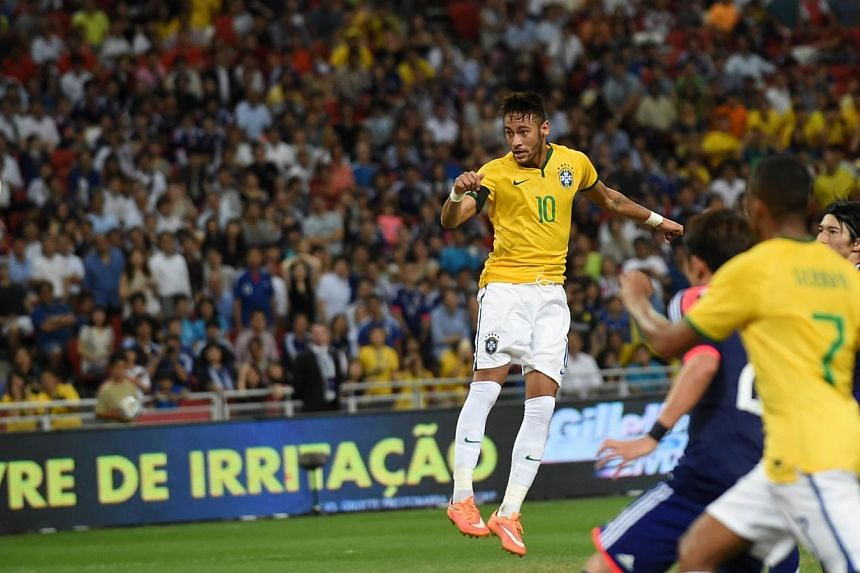 Brazil's forward Neymar heads the ball for his fourth goal against Japan in a friendly football match at the National stadium in Singapore on Oct 14, 2014. -- PHOTO: AFP