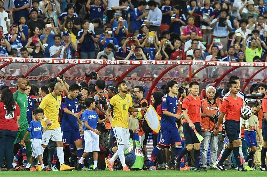 Brazil's forward Neymar (middle in yellow) leads the team onto the pitch before a friendly football match against Japan at the National stadium in Singapore on Oct 14, 2014. -- PHOTO: AFP
