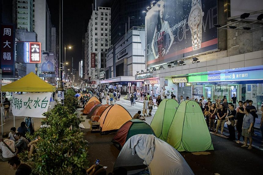 Tents belonging to pro-democracy protesters on a street near one of the Mongkok barricades in Hong Kong on late on Oct 13, 2014. -- PHOTO: AFP