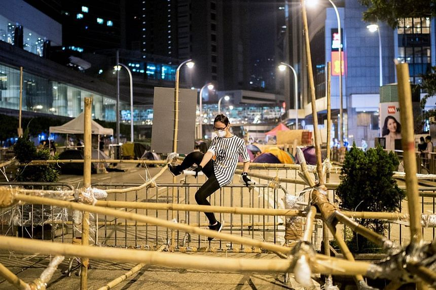 A pro-democracy protester climbs over a barricade blocking a major road in Hong Kong on Oct 14, 2014. -- PHOTO: AFP