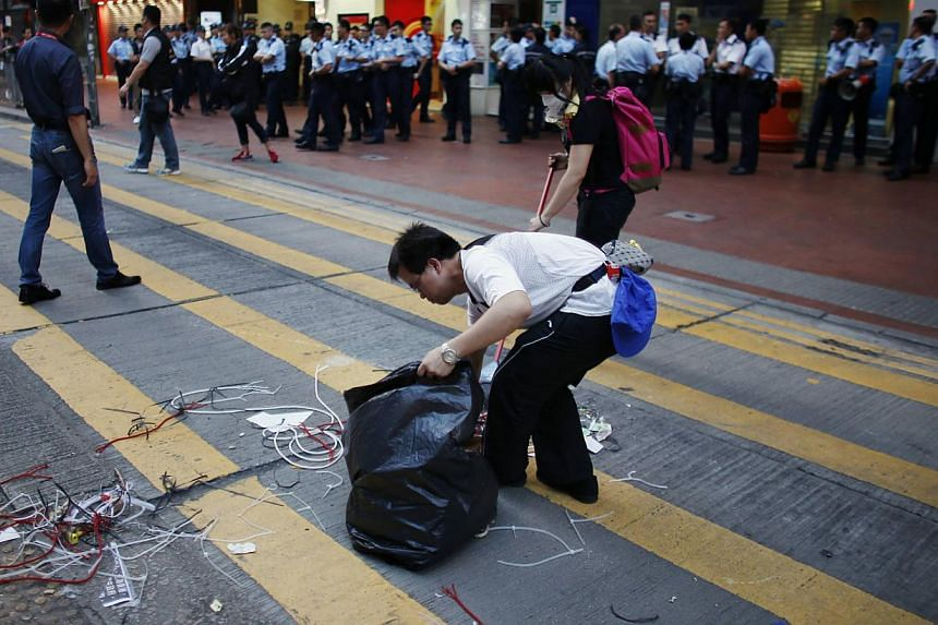 Pro-democracy protesters clean a street after policemen removed some barricades, at a protest site in Causeway Bay in Hong Kong on Oct 14, 2014. -- PHOTO: REUTERS