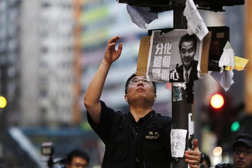 A police official takes down a paper sign after some barricades were removed at a protest site in Causeway Bay in Hong Kong on Oct 14, 2014. -- PHOTO: REUTERS