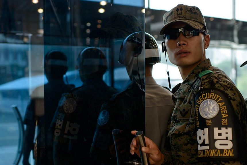 A South Korean soldier at the north-facing entrance to Freedom House, beside the military demarcation line seperating North and South Korea within the Joint Security Area (JSA) at Panmunjom on July 27, 2014. North and South Korea held their first hig