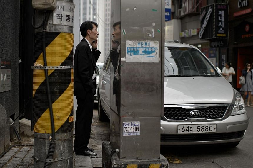 A man talks on a mobile phone in an alleyway in Seoul. South Korea's central bank has cut its benchmark interest rate to the lowest level since 2010. -- PHOTO: AFP
