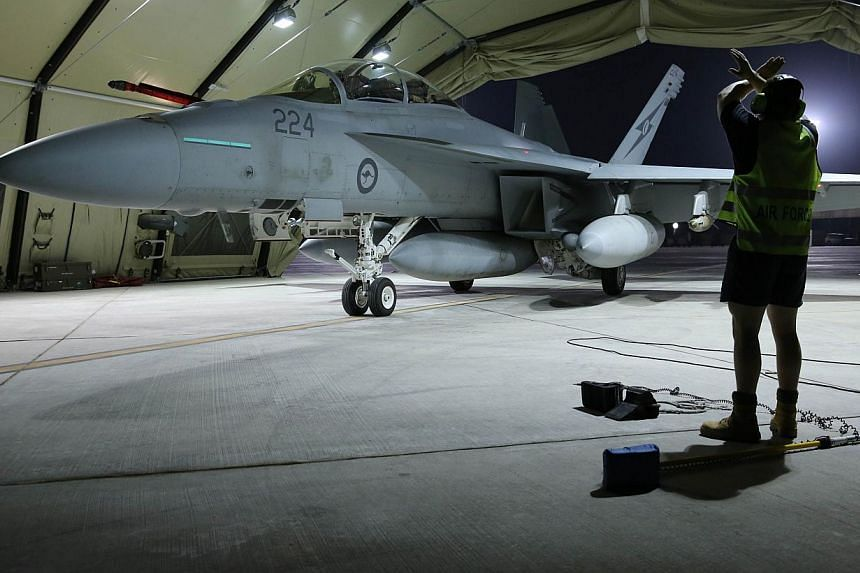 A Royal Australian Air Force F/A-18F Super Hornet aircraft coming to a stop in its hangar in the Middle East. -- PHOTO: AFP