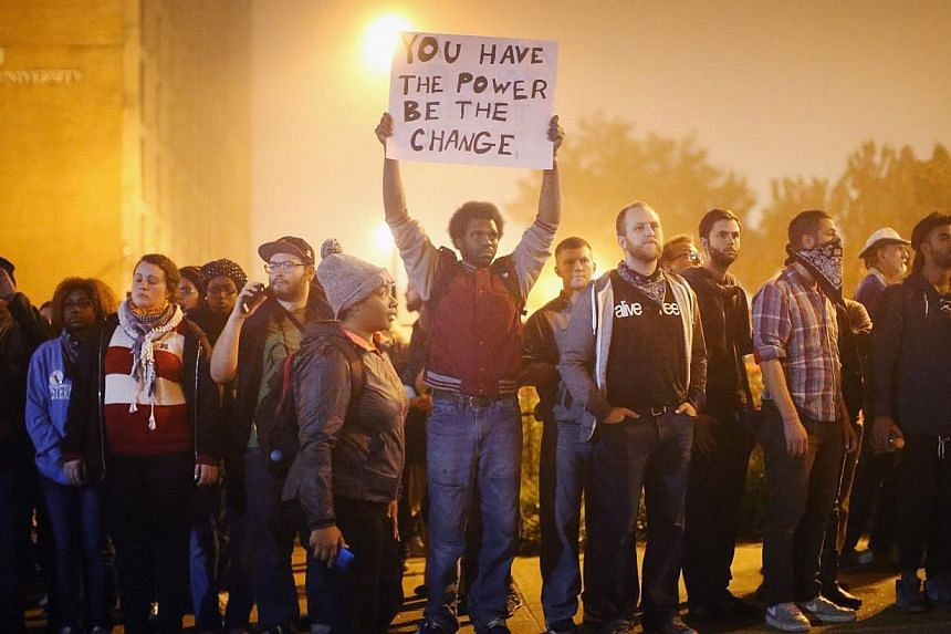 Demonstrators march through the street on Oct 13, 2014, in St Louis, Missouri. -- PHOTO: AFP