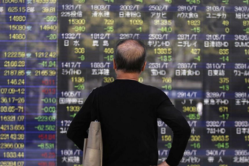 A pedestrian looks at an electronic board showing various stock prices outside a brokerage in Tokyo, Japan. -- PHOTO: REUTERS