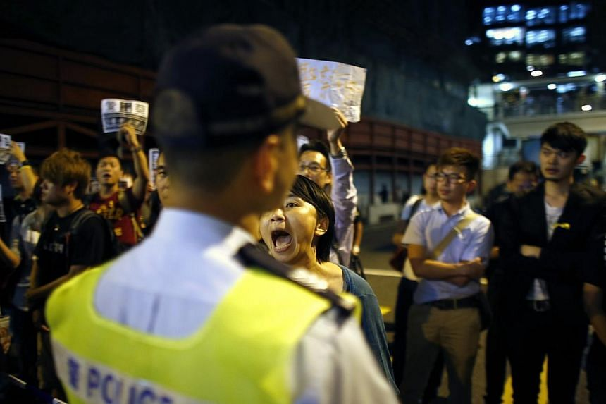A pro-democracy protester yells at a police officer as she block a street at the entrance of police headquarters at Wan Chai district in Hong Kong on Oct 15, 2014.British Prime Minister David Cameron said on Wednesday that Britain should stand