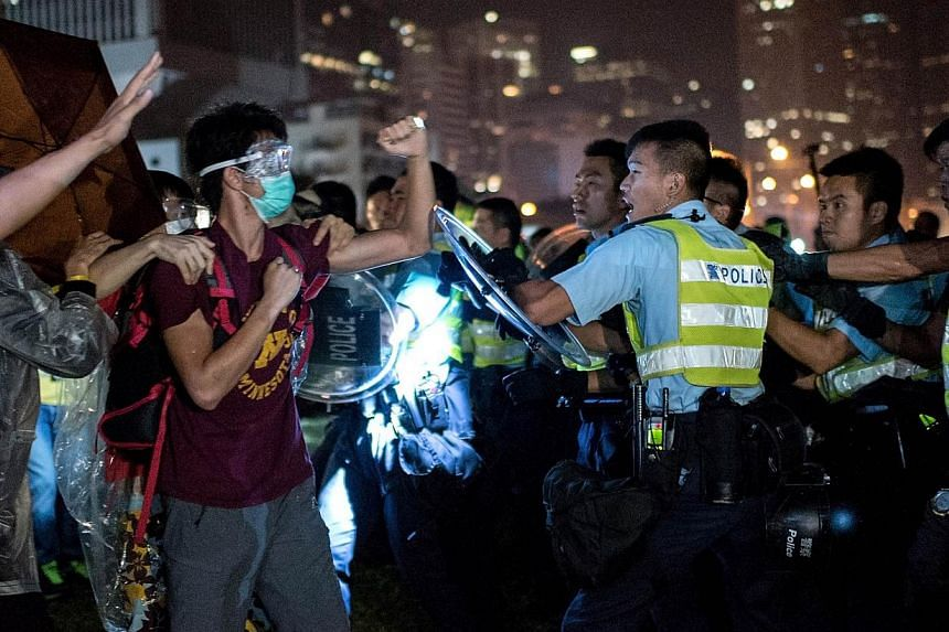 A pro-democracy protester (second, left) shakes his fist at police officers as they advance in Hong Kong on Oct 15, 2014.The BBC's website was blocked in China on Wednesday, one day after a video of Hong Kong police beating and kicking a pro-de