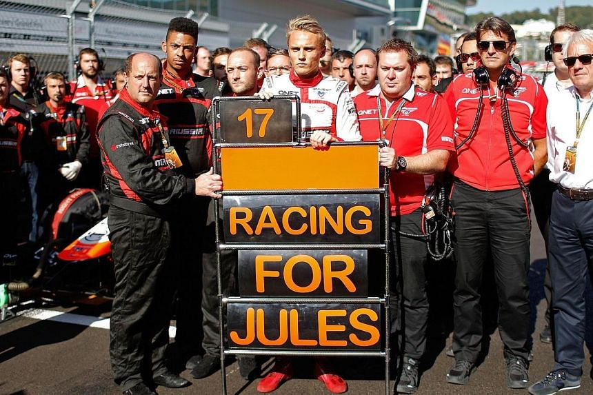 British Formula One driver Max Chilton (centre) of Marussia F1 Team and his team members stand in respect for French Formula One driver Jules Bianchi of Marussia F1 Team at the Sochi autodrom circuit in Sochi on Oct 12, 2014.The Marussia Formul