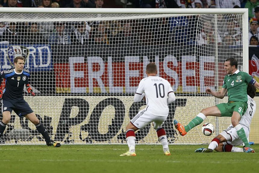 Ireland's John O'Shea (right) scores past Germany's Manuel Neuer (left) during their Euro 2016 Group D qualification soccer match in Gelsenkirchen, Oct 14, 2014. -- PHOTO: REUTERS