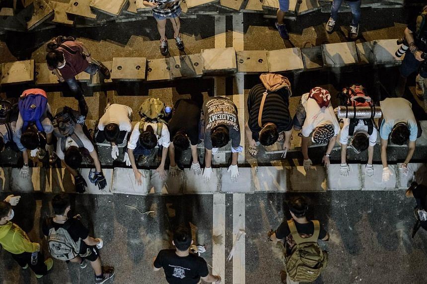 Pro-democracy protester block a road with concrete blocks outside the central government offices in Hong Kong, on Oct 15, 2014. -- PHOTO: AFP
