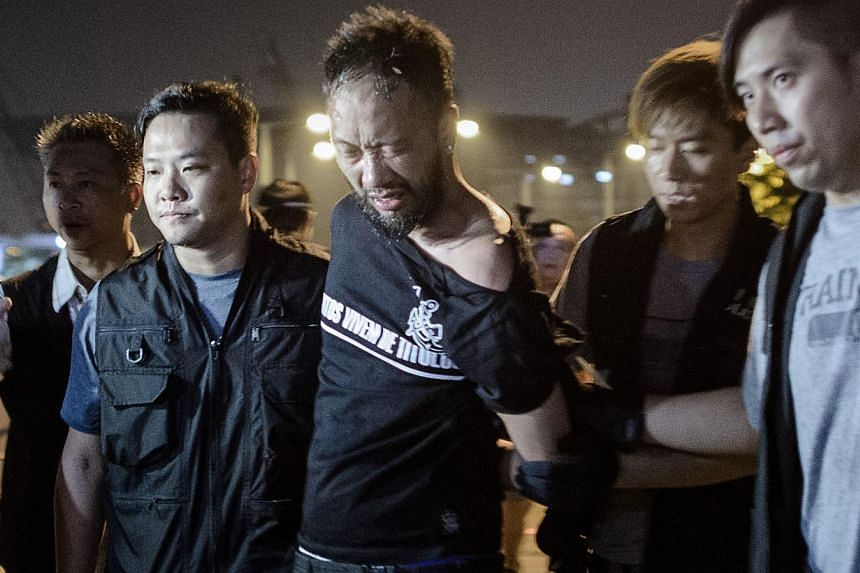 Civic Party member Ken Tsang, one of Hong Kong's pro-democracy political groups, is taken away by policemen, before being allegedly beaten up by police forces as seen on local TV footage shot outside the central government offices in Hong Kong, on Oc