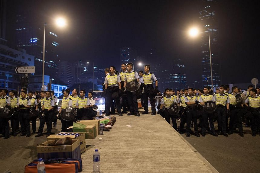Police prepare to confront pro-democracy protesters outside the central government offices in the Admiralty district of Hong Kong, on Oct 15, 2014. -- PHOTO: AFP