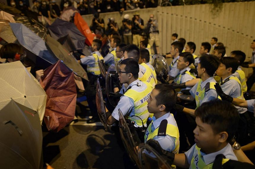 Police confront pro-democracy protesters outside the central government offices in the Admiralty district of Hong Kong, on Oct 15, 2014. -- PHOTO: AFP