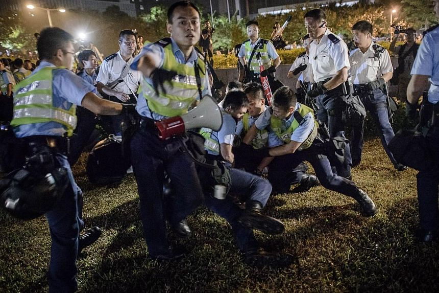 Police forces arrest pro-democracy protesters outside the central government offices in Hong Kong on Oct 14, 2014. -- PHOTO: AFP