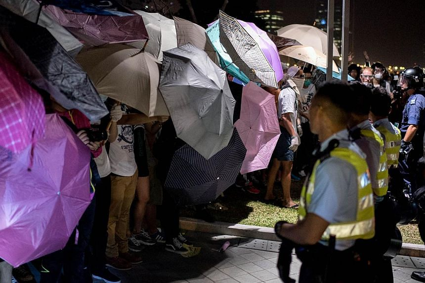 Pro-democracy protesters stand behind umbrellas as police prepare to advance on their positions near the central government offices in Hong Kong on Oct 15, 2014. -- PHOTO: AFP