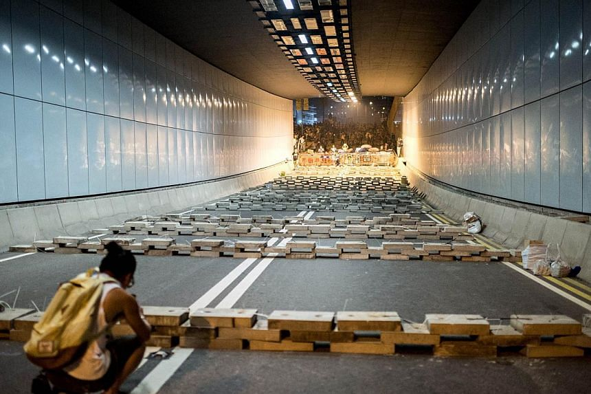 A pro-democracy protester takes photos of obstacles made with concrete slabs in a tunnel near the central government offices in Hong Kong on Oct 15, 2014. -- PHOTO: AFP