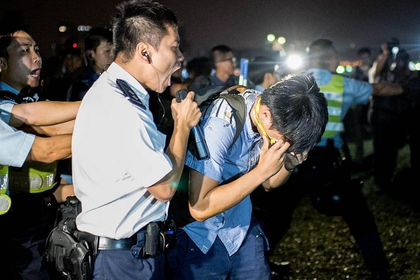 A police officer shouts at a pro-democracy protester after he was hit with pepper spray in Hong Kong on Oct 15, 2014. -- PHOTO: AFP