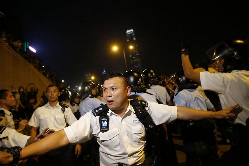 Police retreat after confronting pro-democracy protesters near the government headquarters in Hong Kong on Oct 14, 2014. -- PHOTO: REUTERS