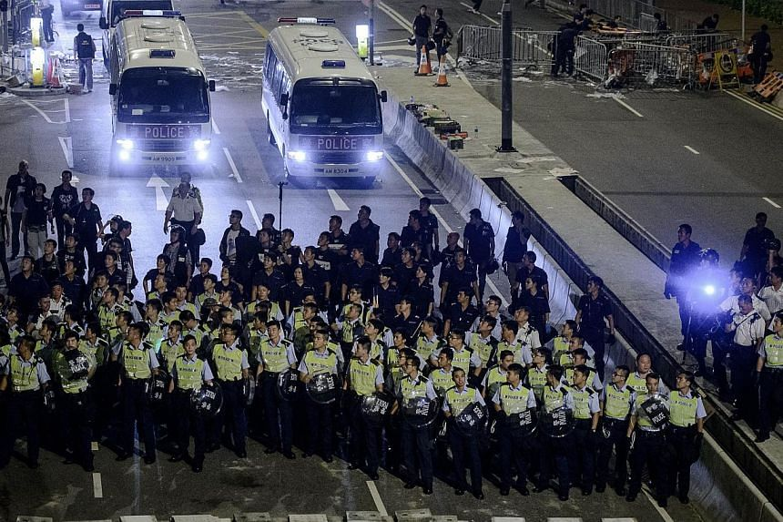 Police forces march toward pro-democracy protesters during a standoff outside the central government offices in Hong Kong on Oct 14, 2014. -- PHOTO: AFP