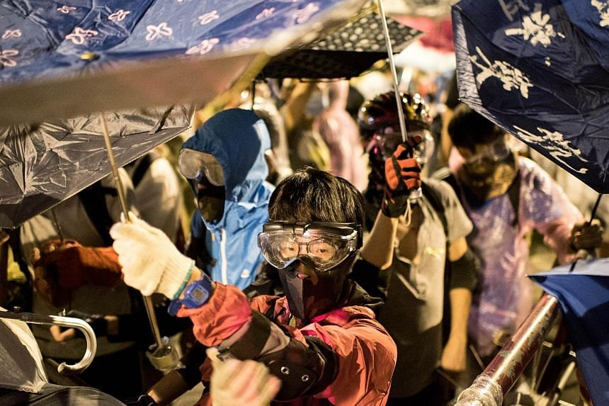 Pro-democracy protesters stand behind umbrellas as police advance on their positions near the central government offices in Hong Kong on Oct 15, 2014. -- PHOTO: AFP