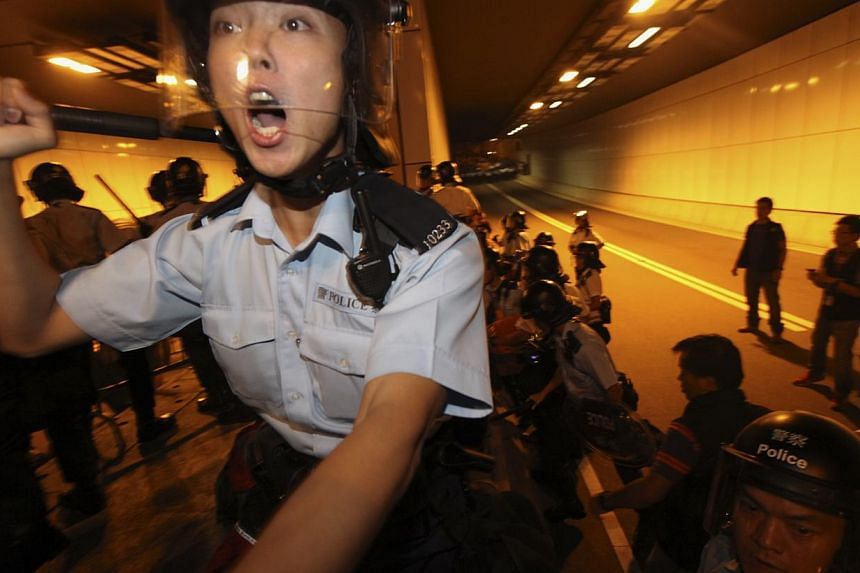 A riot policeman springing into action as pro-democracy protesters storm into a vehicle tunnel to block a road leading to the financial Central district in Hong Kong Oct 14, 2014. -- PHOTO: REUTERS