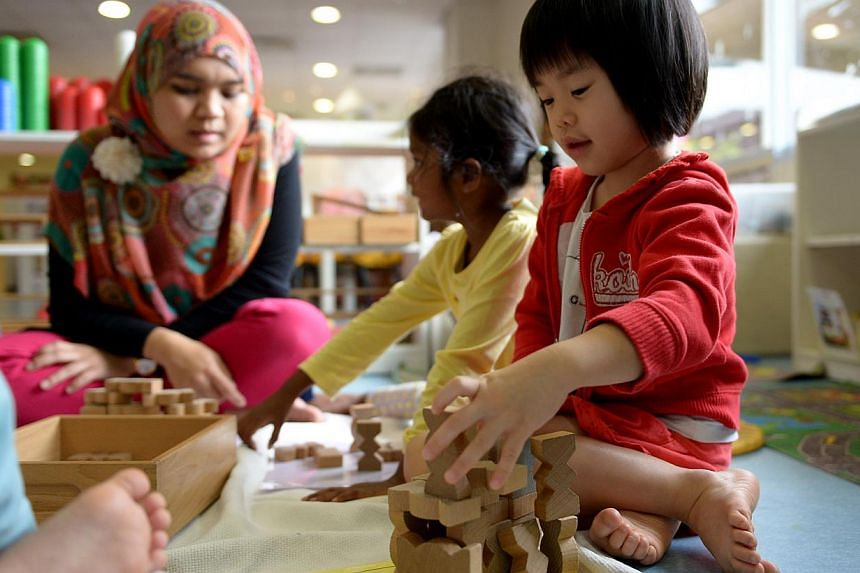 Ng Le Qi (right) playing with wooden blocks in a block play experience being facilitated by Farhana Kamal Beck (left), English teacher at The Caterpillar's Cove, a childcare centre which NTUC First Campus runs in Ngee Ann Polytechnic. -- PHOTO: ST FI