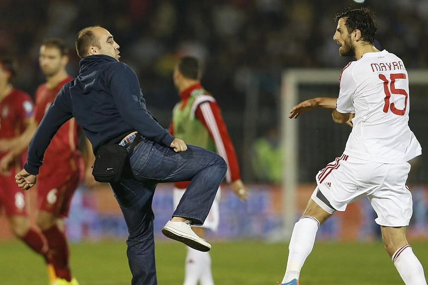 A Serbian fan scuffles with Albania's Mergim Mavraj during the Euro 2016 Group I qualifying soccer match at the FK Partizan stadium in Belgrade on Oct 14, 2014. -- PHOTO: REUTERS