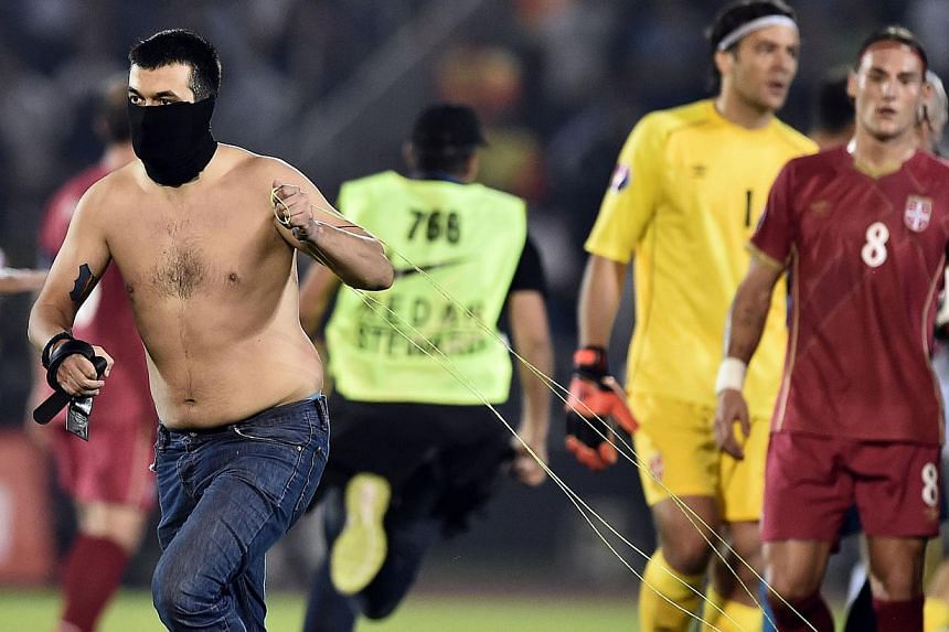 A masked Serbian supporter pulls a drone after a flag with Albanian national symbols was flown over the pitch and pulled down by Serbia's players during the Euro 2016 group I football match between Serbia and Albania in Belgrade on Oct 14, 2014. -- P
