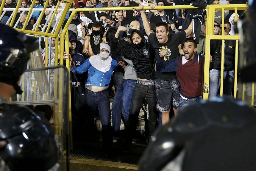 Serbian fans confront riot police during the Euro 2016 Group I qualifying soccer match between Serbia and Albania at the FK Partizan stadium in Belgrade on Oct 14, 2014. -- PHOTO: REUTERS