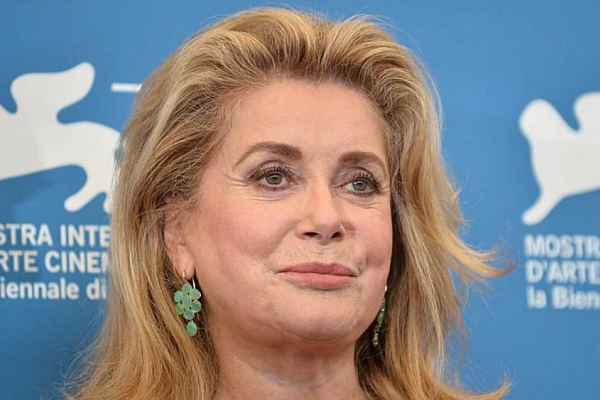 """French actress Catherine Deneuve poses during the photocall of the movie 3 Coeurs presented in competition at the 71st Venice Film Festival on Aug 30, 2014 at Venice Lido. Deneuve said on Tuesday she was """"pleased and touched"""" to accept a lifetime ach"""