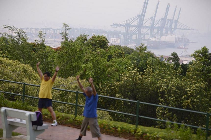 Men exercise at Kent Ridge Park with the Pasir Panjang PSA Terminal in the background at around 7am on 15 Oct, 2014. The overall PSI reading in Singapore at 7am was 67-72.-- ST PHOTO:MARK CHEONG