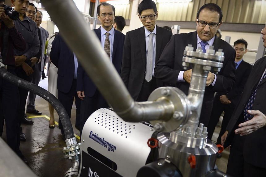 Second Minister for Home Affairs and Trade & Industry S Iswaran (middle) takes a look at a multiphase flowmeter prototype during a tour of the NUS Multiphase Flow Loop Facility on Oct 15, 2014. -- ST PHOTO: MARK CHEONG