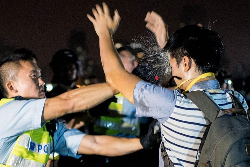 A police officer sprays a pro-democracy protester in the face with pepper spray in Hong Kong on Oct 15, 2014.Hong Kong police and protesters clashed early on Wednesday in some of the most violent incidents since pro-democracy demonstrations beg