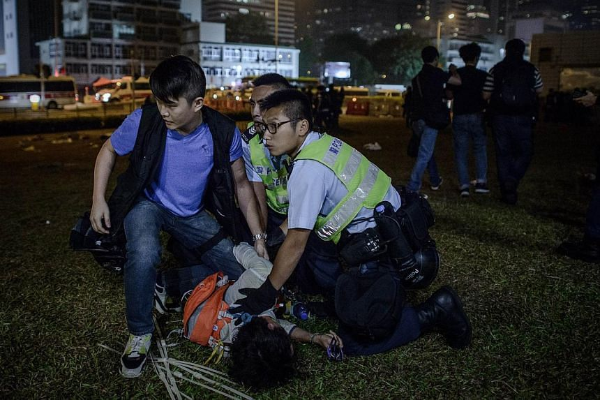 Police forces arrest a pro-democracy protester outside the central government offices in Hong Kong on Oct 14, 2014. Hong Kong police and protesters clashed early on Wednesday in some of the most violent incidents since pro-democracy demonstrations be