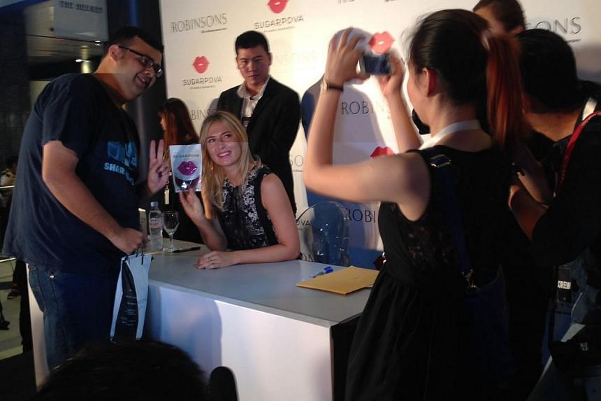Maria Sharapova autographing packets of her newly launched candy line Sugarpova at Robinsons The Heeren. -- ST PHOTO: CAROLINE CHIA