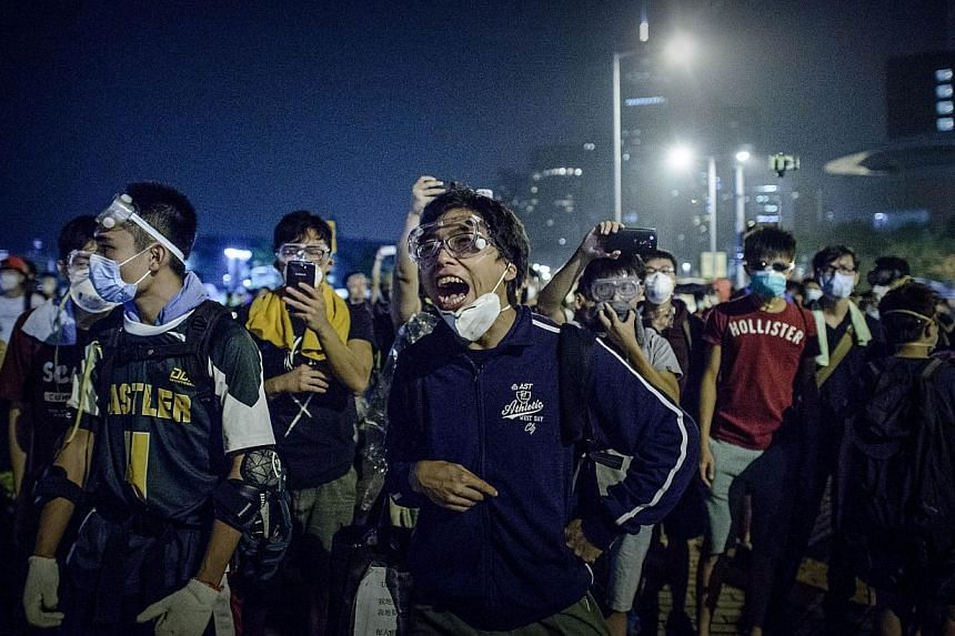 Pro-democracy protesters shout at police forces outside the central government offices in Hong Kong on Oct 14, 2014.Hong Kong police and protesters clashed early on Wednesday in some of the most violent incidents since pro-democracy demonstrati