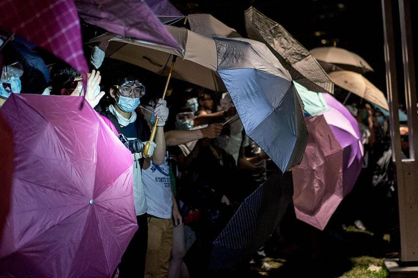 Pro-democracy protesters stand behind umbrellas as police advance on their positions near the central government offices in Hong Kong on Oct 15, 2014. Hong Kong police and protesters clashed early on Wednesday in some of the most violent inciden