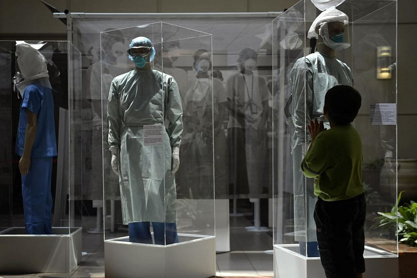 A boy looks at mannequins in protective outfits worn by health-care staff during the 2003 Sars outbreak at the atrium of the Tan Tock Seng Hospital. -- PHOTO: ST FILE