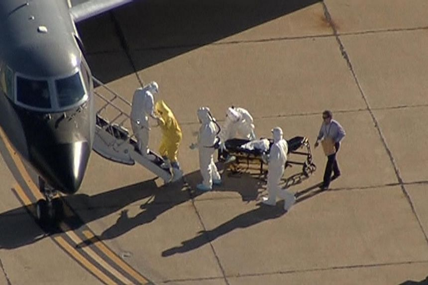 Texas nurse Amber Vinson is helped up the steps of a waiting aircraft by personnel in this still image taken from video courtesy of NBC5- KXAS in Dallas, Texas on Oct 15, 2014. -- PHOTO: REUTERS