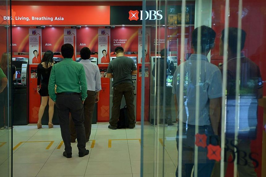 People queueing up at DBS Bank Automated Teller Machines (ATMs) at Shenton Way on Sept 11, 2013.DBS Bank has launched a new service to enable its customers to access simple transactions from their accounts using SMSes. -- PHOTO: ST FILE