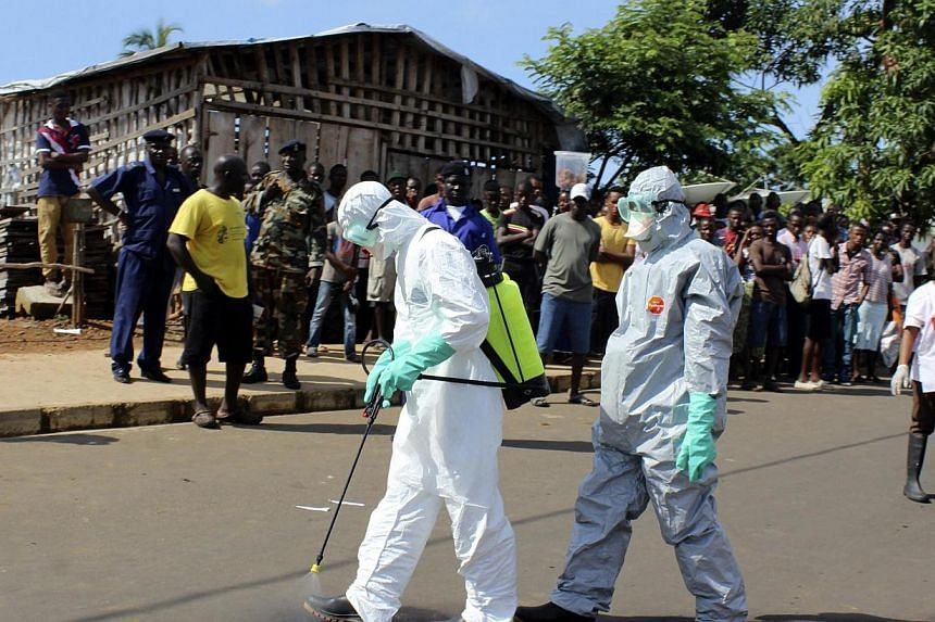 Health workers spray themselves with chlorine disinfectants after removing the body a woman who died of Ebola virus in the Aberdeen district of Freetown, Sierra Leone on Oct 14, 2014.-- PHOTO: REUTERS