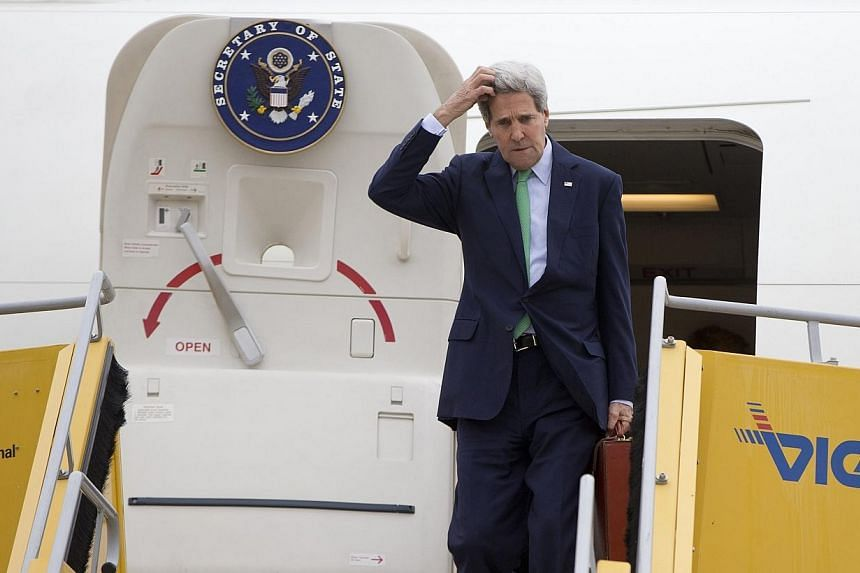 US Secretary of State John Kerry steps out from his plane as he arrives at Vienna International Airport in Vienna on Oct 15, 2014. Globe-trotting top US diplomat John Kerry was left hoofing it back on a commercial flight from Vienna Thursday, af
