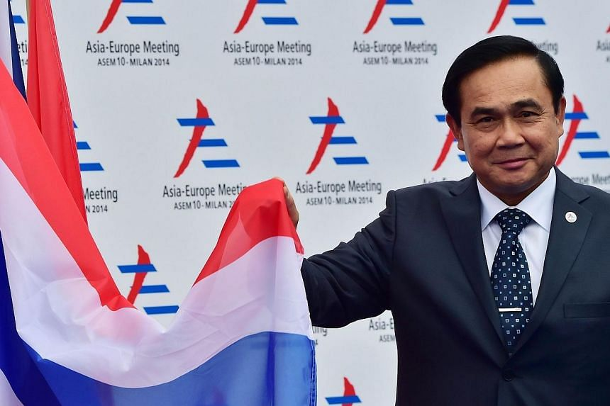 Thai junta leader and Prime Minister Prayuth Chan Ocha poses next to the Thai flag as he arrives to attend the 10th Asia-Europe Meeting (ASEM) on Oct 16, 2014, in Milan.Mr Prayuth slipped quietly into the club of world leaders Thursday against