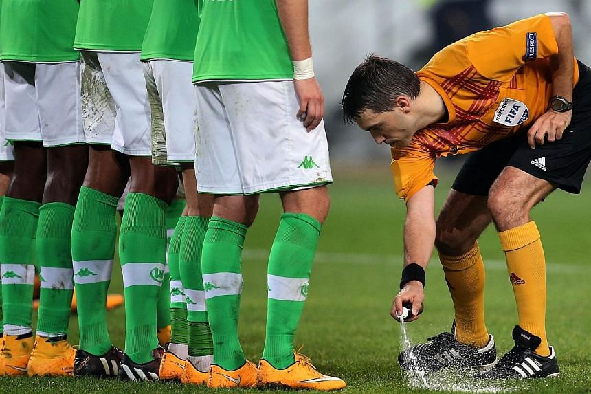 Romanian referee Ovidiu Alin Hategan sprays a temporary line for a free kick as Wolfsburg assemble a wall during the UEFA Europa League group H football match between VfL Wolfsburg v LOSC Lille on Oct 2, 2014 in Wolfsburg.Vanishing spray is to